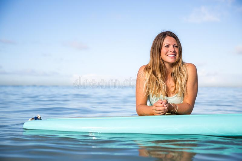 Athlete chilling on her paddle board in Hawaii royalty free stock photography