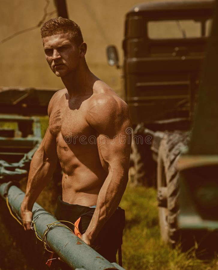 Athlete concept. Athlete man pull truck trailer. Strong athlete on construction site. Athlete with six pack and ab on. Muscular torso royalty free stock image