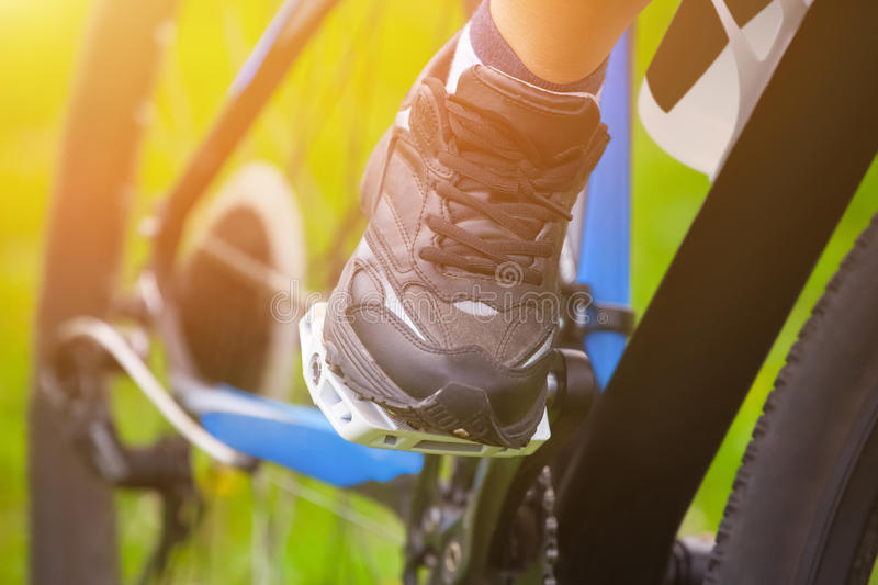 Athlete - cyclist keeps his feet in running shoes on the pedals of his vehicle while driving. The concept of sports, a healthy and active lifestyle stock photos