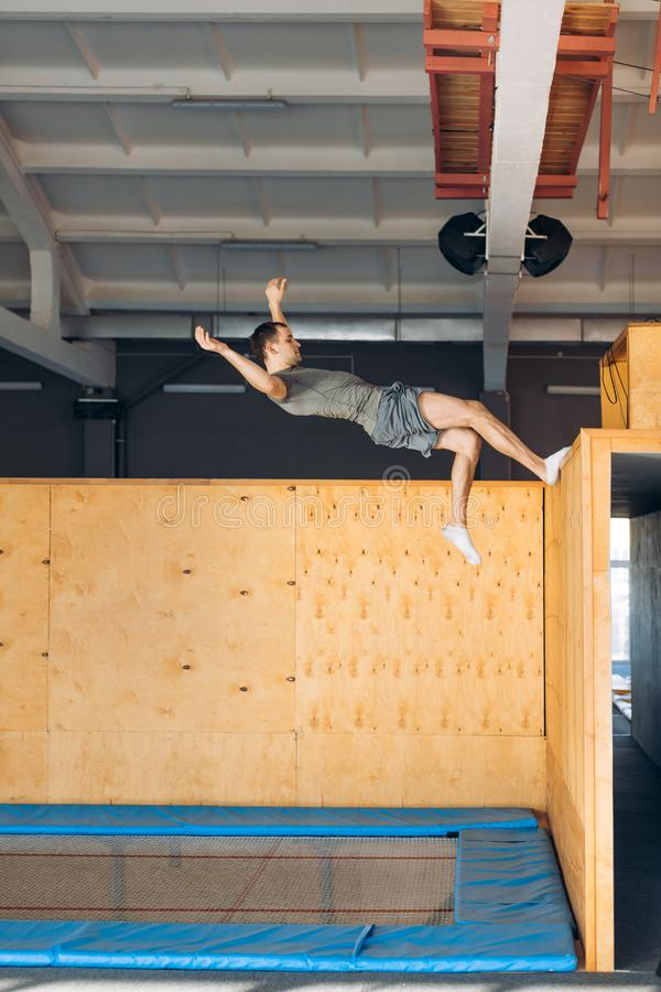 Athlete is doing exercise on the air after pushing off the wooden board royalty free stock photos