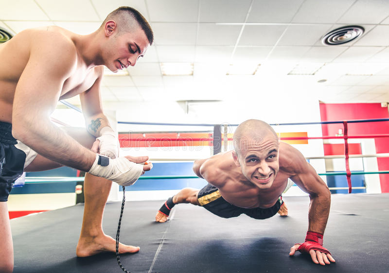 Athlete doing push ups. Muay thai fighter doing push ups - Coach training his athlete for a boxe match - Sportive men working out in a martial arts gym royalty free stock photo