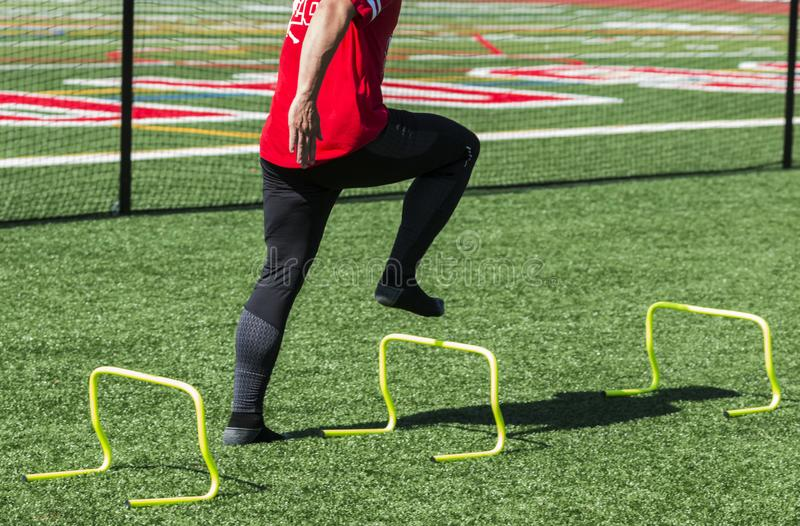 Athlete doing strength and speed drills with no shoes on. A high school track and field athlete is steping over yellow mini hurdles with no shoes on to help royalty free stock images