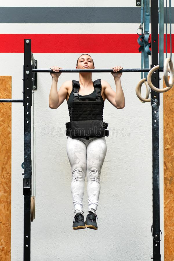 Athlete doing weighted pull-ups on a bar. Young woman athlete doing weighted pull-ups on a bar wearing a heavy jacket to strengthen her upper body muscles in a royalty free stock photos