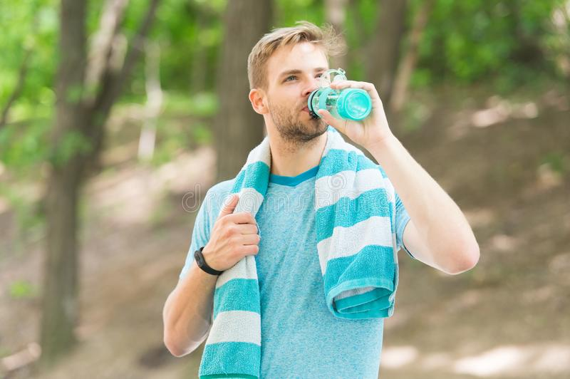 Athlete drink water. Water balance. Athlete hold bottle care hydration body. Thirsty after morning jog. Refreshing. Vitamin drink after great workout. Man stock image