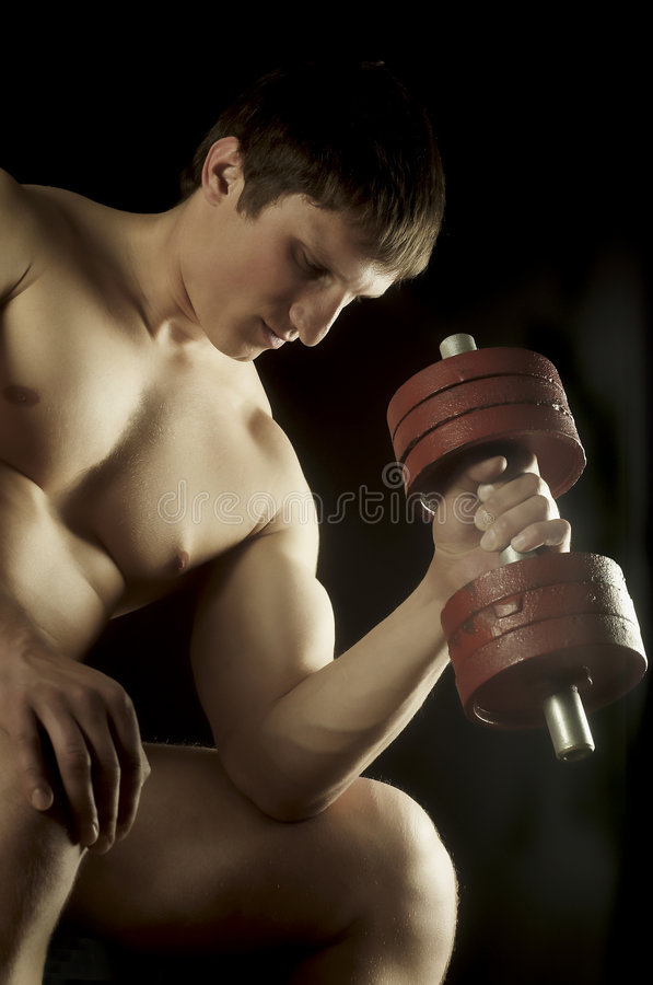 Athlete with dumbbells. The young man of an athletic constitution plays sports royalty free stock photos