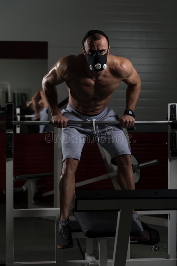 Athlete Exercising Push-Ups On Barbell In Elevation Mask. Bodybuilder Doing Push Ups On Barbell As Part Of Bodybuilding Training In Elevation Mask stock images