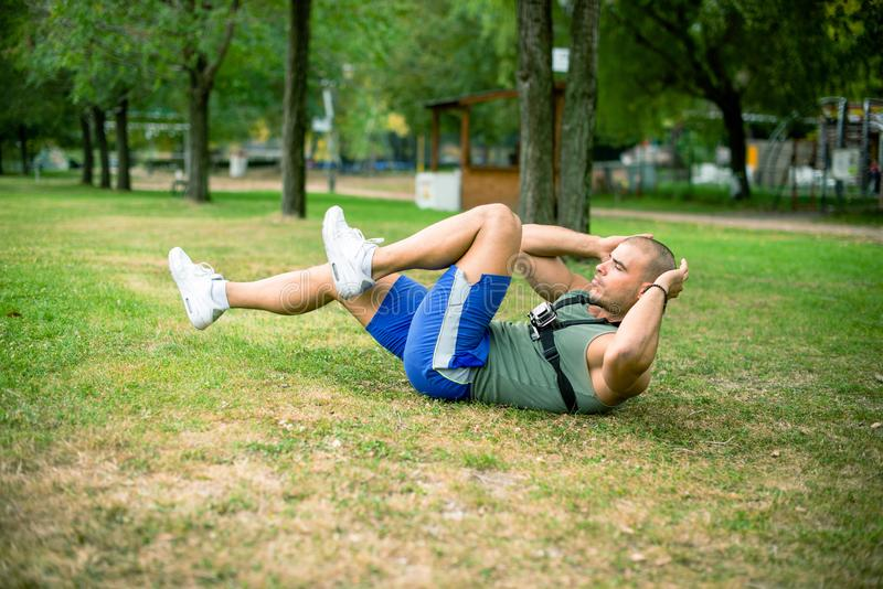 Athlete exercising sit-ups in park. royalty free stock photos
