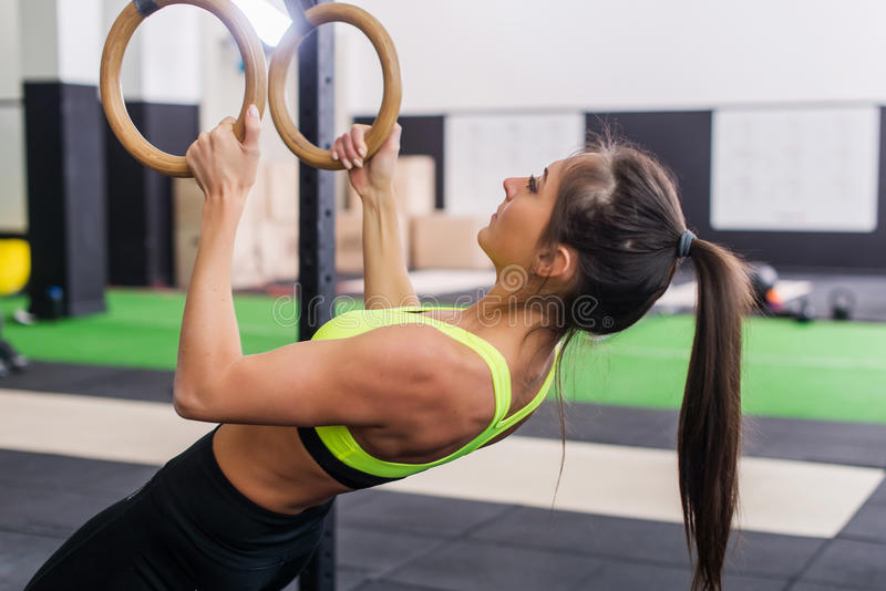 Athlete fit woman exercising in gym pulling up on gymnastic rings side view. stock image