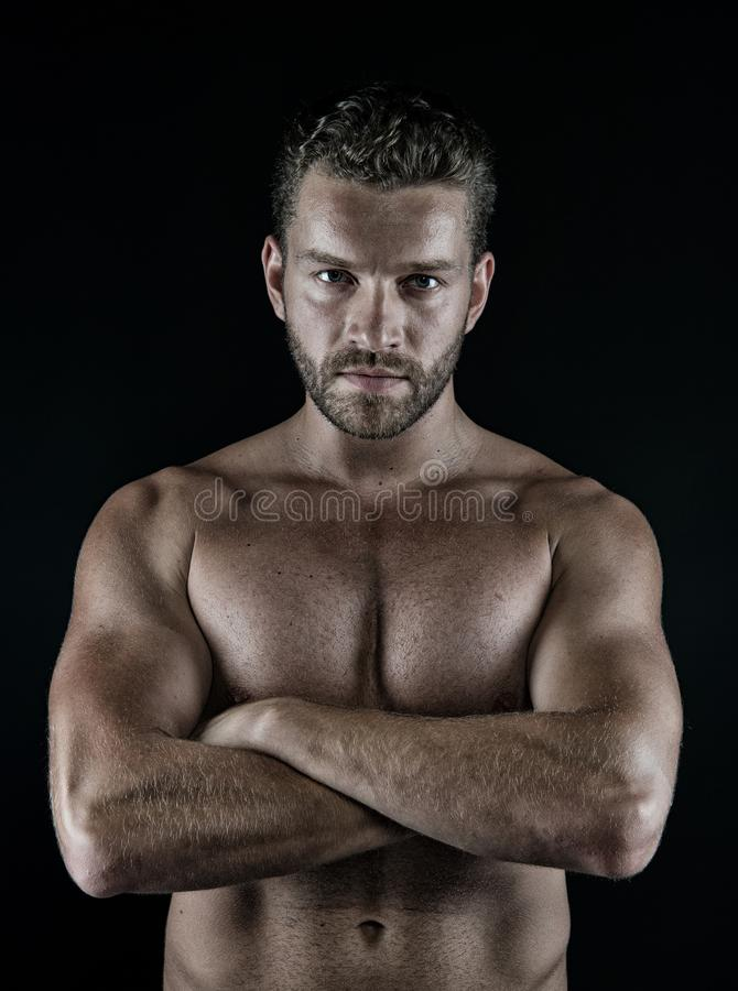 Athlete with folded hands on muscular bare torso, chest, belly. Muscles, biceps, triceps standing on black background. Fitness, bodybuilding and sport. Power stock photo