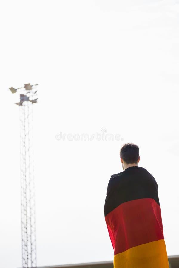 Athlete with german flag wrapped around his body royalty free stock photos