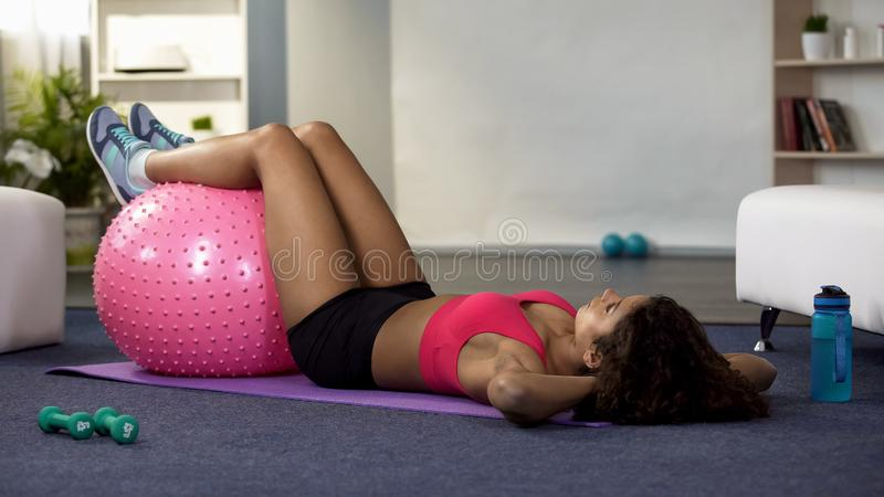Athlete girl doing abdominal exercise with fitness ball at home, health care stock photos