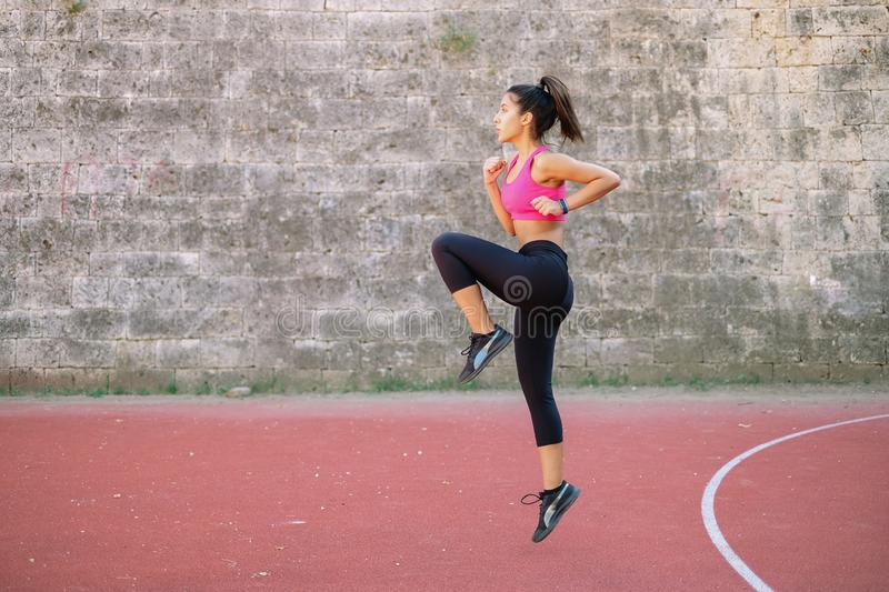 Athlete girl jumping high and rising knee stock photo
