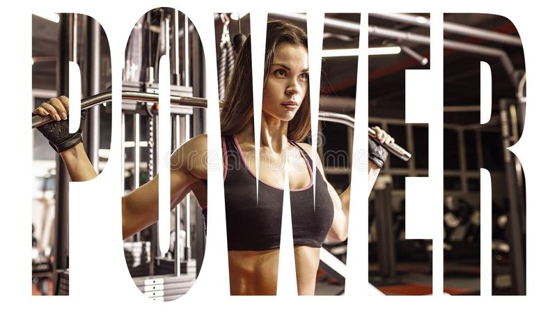 Athlete girl in sportswear working out and training her arms and shoulders with exercise machine in gym. Motivation sign. royalty free stock images
