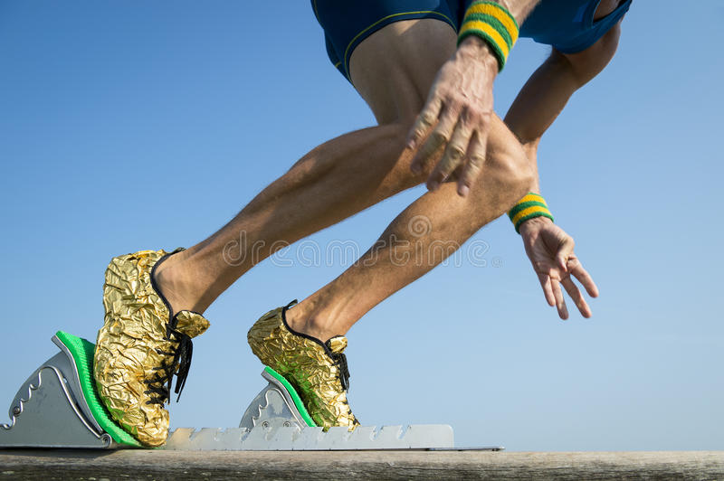 Athlete with Gold Running Shoes Starting a Race. Athlete weariing gold running shoes takes off in a blur from from the race track starting blocks stock photo