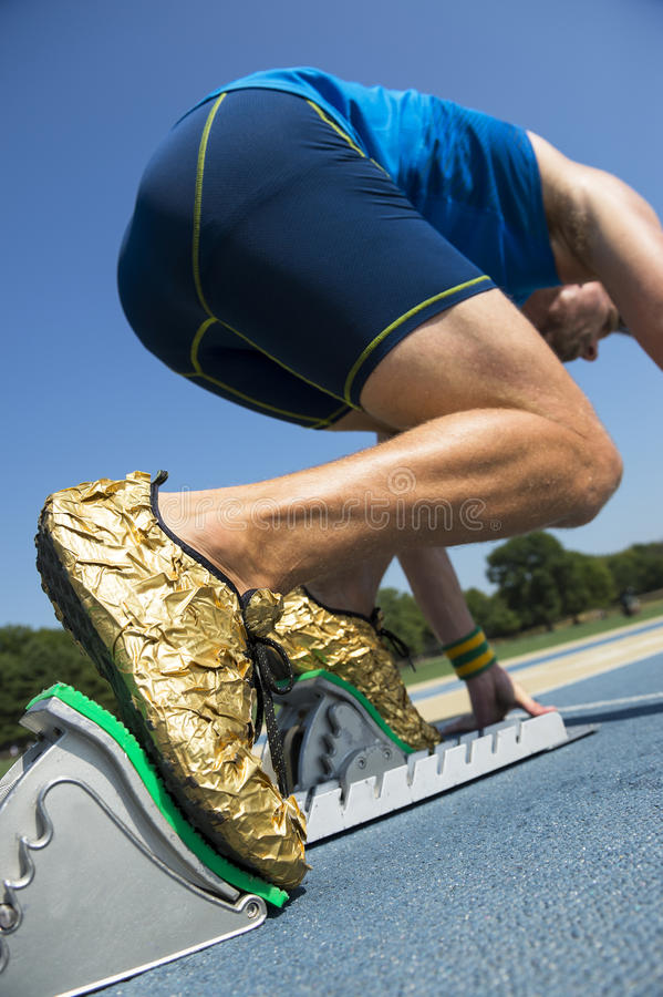 Athlete in Gold Shoes on Starting Blocks. Athlete in gold shoes starting a race from the starting blocks on a blue running track stock photo