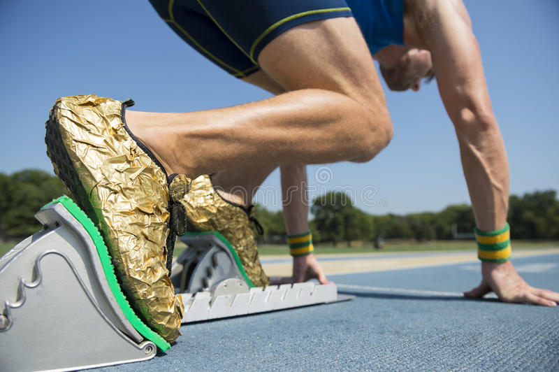 Athlete in Gold Shoes on Starting Blocks. Athlete in gold shoes starting a race from the starting blocks on a blue running track stock image