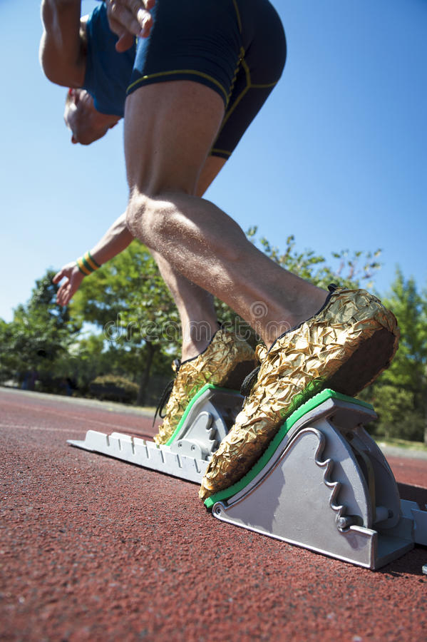 Athlete in Gold Shoes on Starting Blocks. Athlete in gold shoes starting a race from the starting blocks on a red running track stock photography
