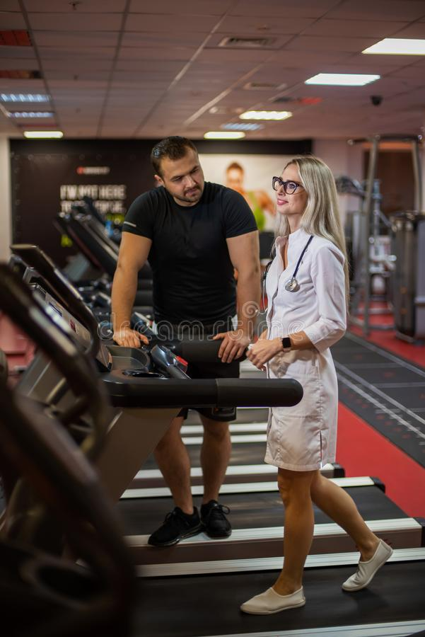 The athlete in the gym controls the treadmill exercises of a beautiful female doctor in medical uniform. The gym coach royalty free stock image