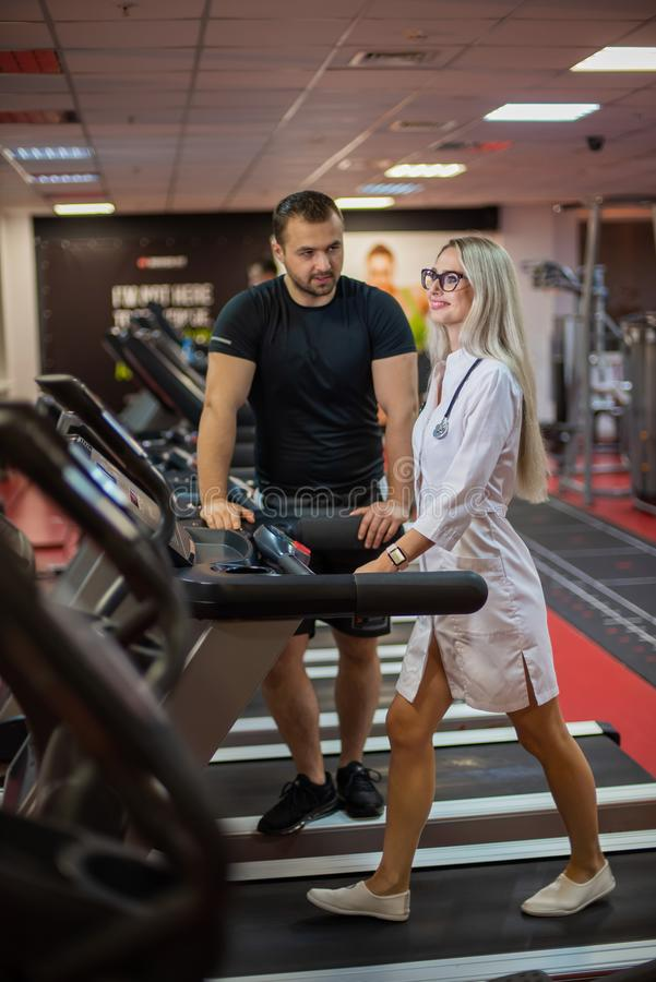 The athlete in the gym controls the treadmill exercises of a beautiful female doctor in medical uniform. The gym coach stock images