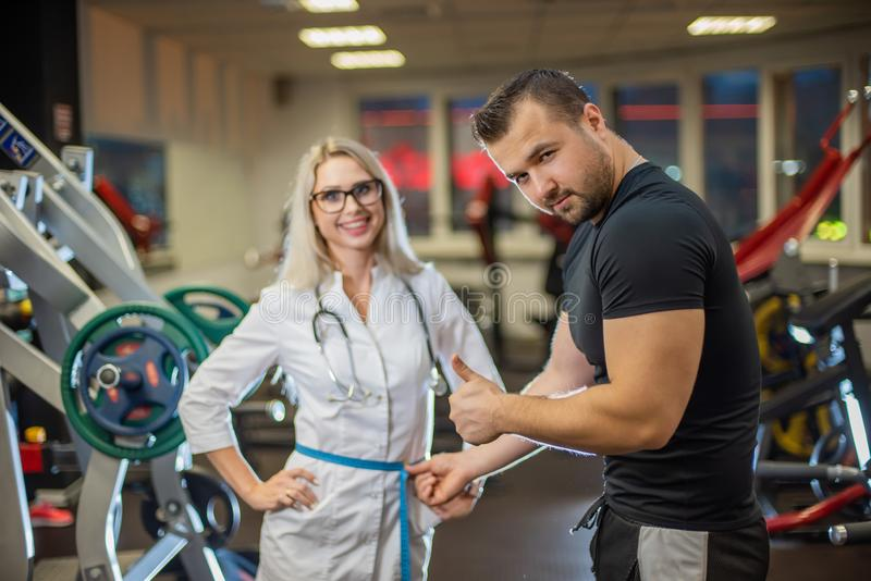 The athlete in the gym measures with a centimeter tape the waist volume of a beautiful female doctor in medical uniform royalty free stock photo