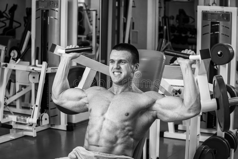 Athlete in the gym. Performing heavy exercise. Training to achieve the desired result. Photos for magazines, posters and Web sites stock image