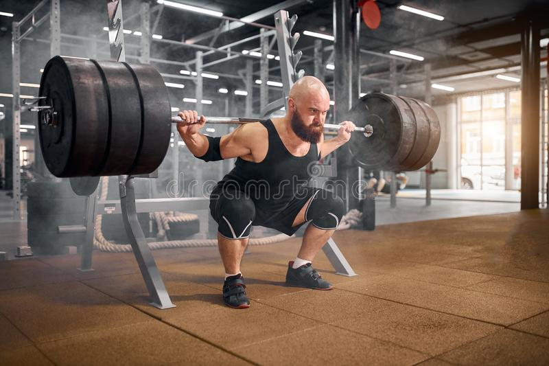 Athlete in the gym is prepared to perform an exercise. Called deadlift, squatting with heavy barbell in professional gym hall, sport bodybuilding concept royalty free stock image