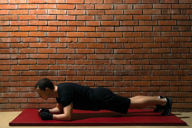 Athlete in the hall doing an exercise on a red mat for training a press against a brick wall background stock photo
