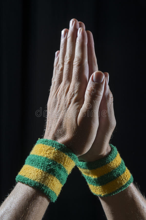 Athlete Hands Wearing Brazil Wristbands Praying. Athlete hands wearing Brazil color yellow and green wristbands held together in prayer against dark background royalty free stock photography