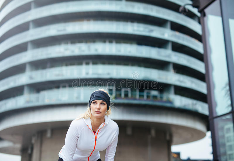 Athlete having a short break from running. Young female exercising on city street royalty free stock photography