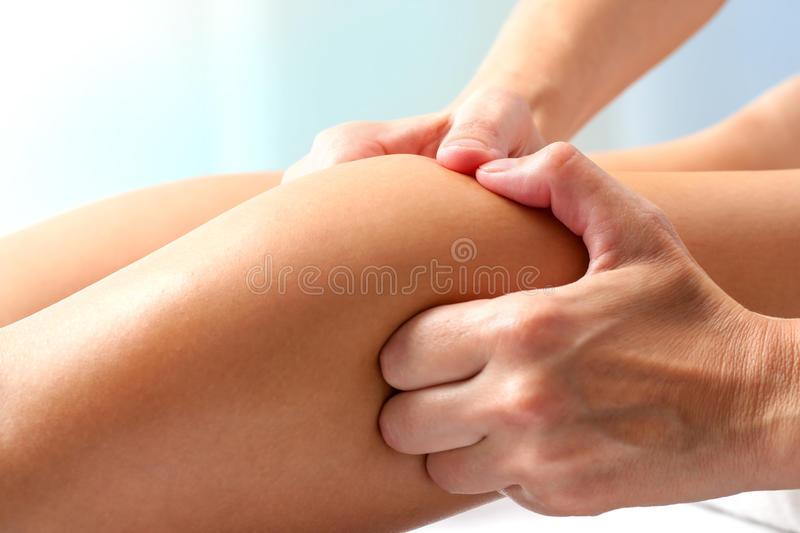 Athlete having therapeutic calf muscle massage. Macro close up of hands doing manipulative healing massage on female calf muscle stock photography