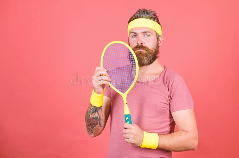 Athlete hipster hold tennis racket in hand red background. Play tennis for fun. Man bearded hipster wear sport outfit. Reach top again. Tennis player retro royalty free stock photography
