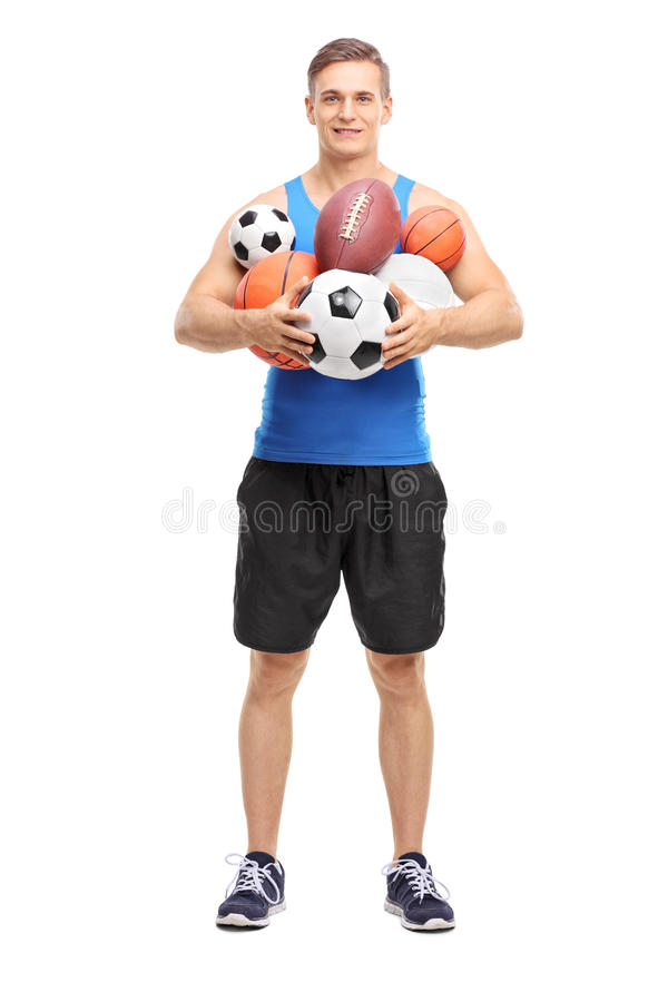 Athlete holding a bunch of different sports balls. Full length portrait of a young athlete holding a bunch of different kinds of sports balls isolated on white royalty free stock images