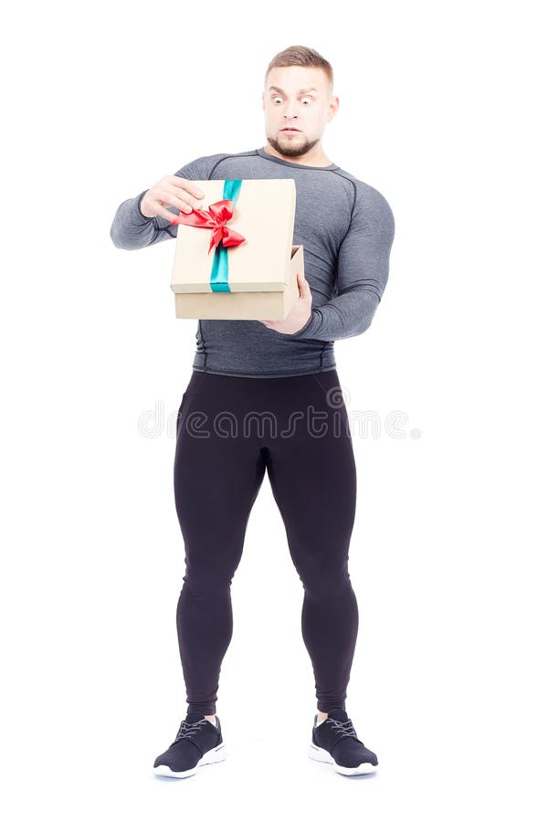 Athlete holding gift box. Portrait of well-muscled athlete posing with gift box on white background royalty free stock image