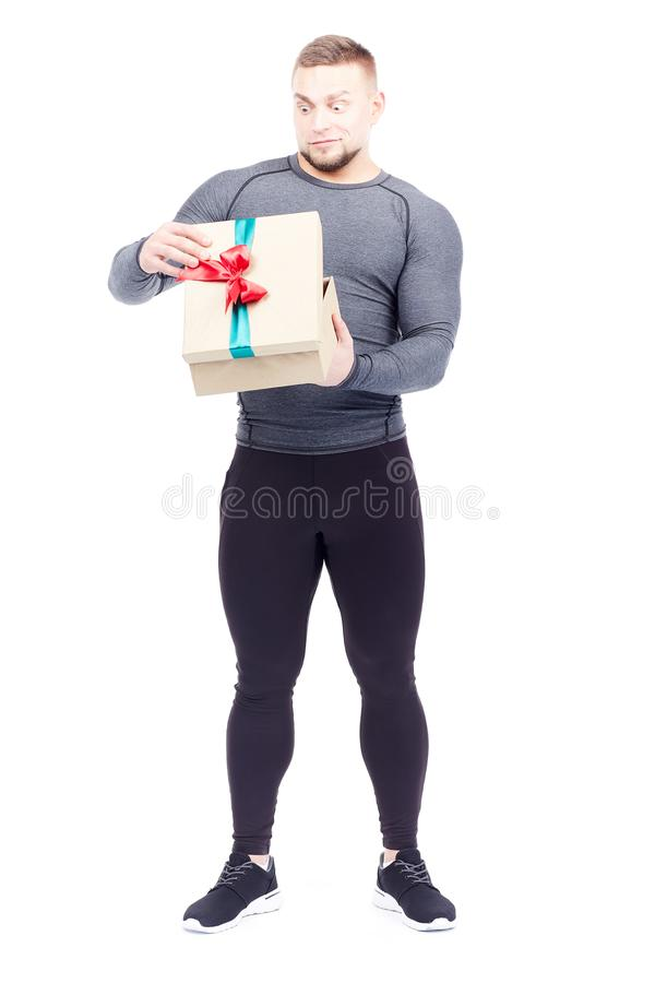 Athlete holding gift box. Portrait of well-muscled athlete posing with gift box on white background royalty free stock photo