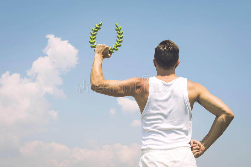 Athlete Holding Laurel Wreath Blue Sky. Athlete in old fashioned white uniform holding laurel wreath against sunny blue sky stock photography