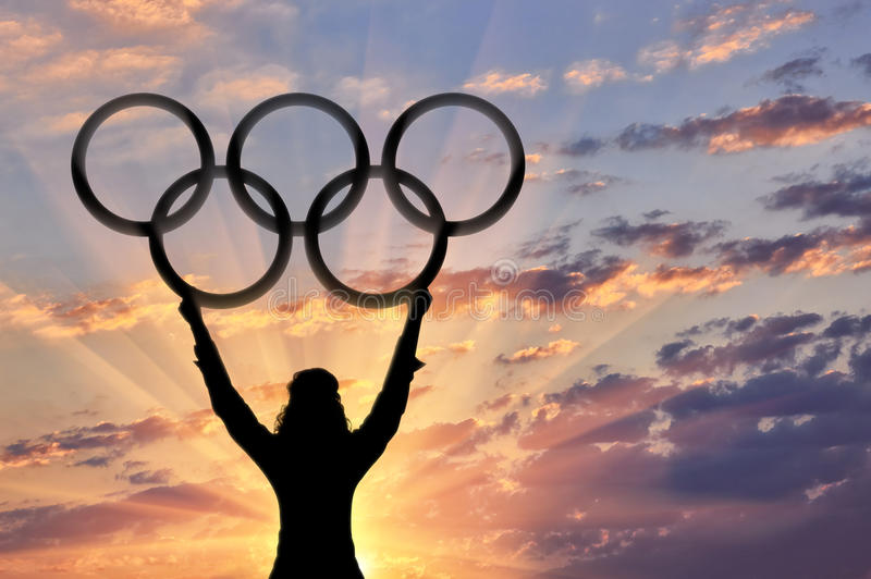 Athlete holding Olympic rings sunset. Athlete raised his hands and holds Olympic rings on sunset background . Sport concept stock photos