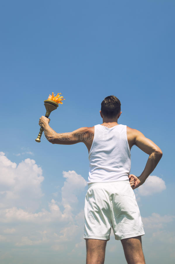 Athlete Holding Sport Torch Blue Sky. Athlete in old fashioned white uniform holding sport torch against sunny blue sky stock images