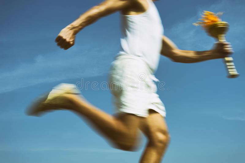 Athlete Holding Sport Torch Blue Sky. Torchbearer in old fashioned white uniform running with sport torch in motion blur across sunny blue sky stock image