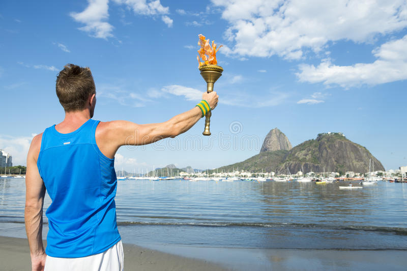 Athlete Holding Sport Torch Rio de Janeiro. Athlete holding sport torch against Rio de Janeiro Brazil skyline with Sugarloaf Mountain royalty free stock image