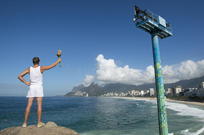 Athlete Holding Sport Torch Rio de Janeiro. Athlete in white uniform standing with sport torch above Rio de Janeiro Brazil skyline at Ipanema Beach royalty free stock photo