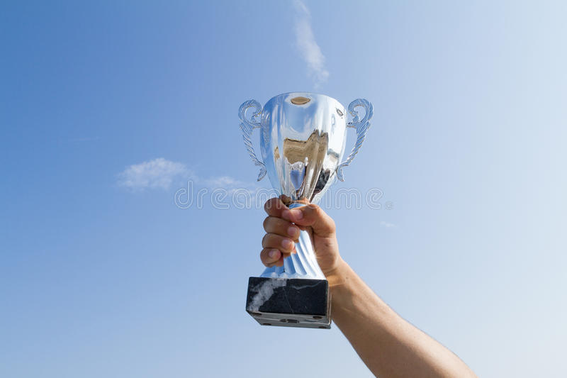Athlete holding up champion winner trophy cup on sky background stock photography