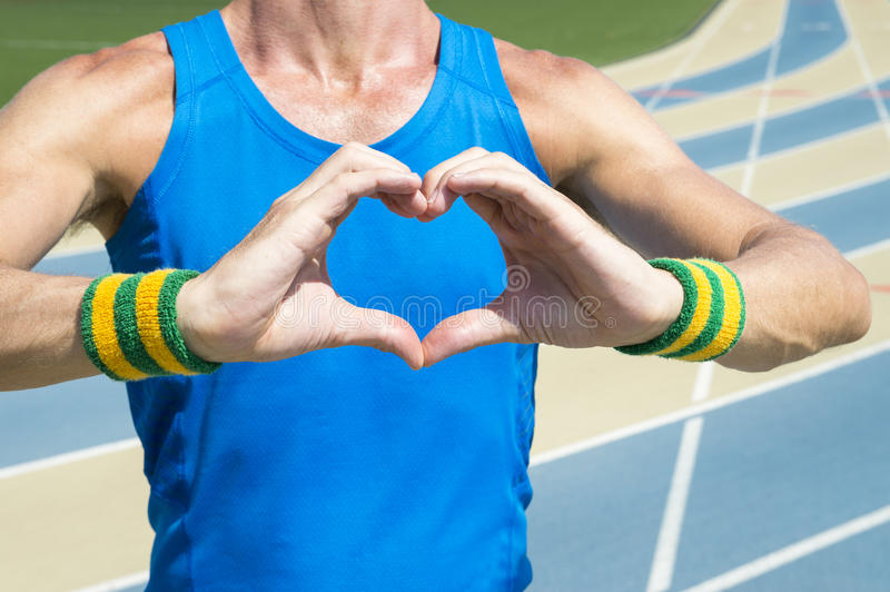 Athlete Holding Up Heart Hands. Athlete in Brazil colored wristbands holding up heart hands at the running track stock images