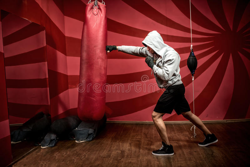 Athlete with hoodie working out at boxing gym, getting ready for fight stock photo