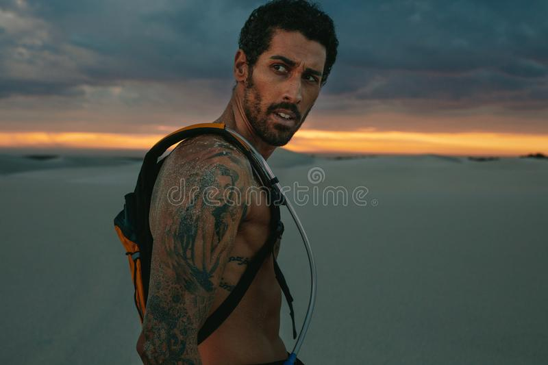 Athlete with hydration pack outdoors at sunset royalty free stock images