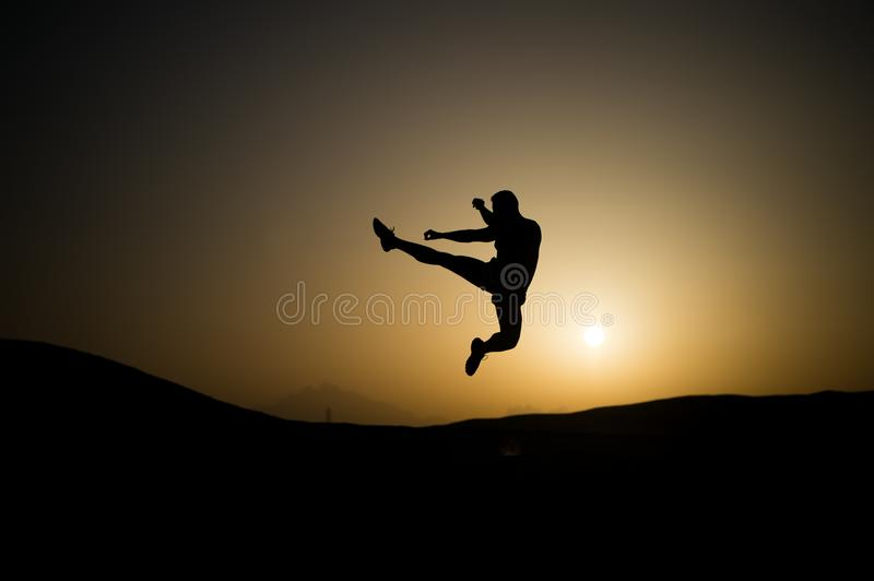 Athlete jump high with energy. Sportsman silhouette on sunset sky. Man training on natural landscape. Workout in summer dusk. Spor stock photography