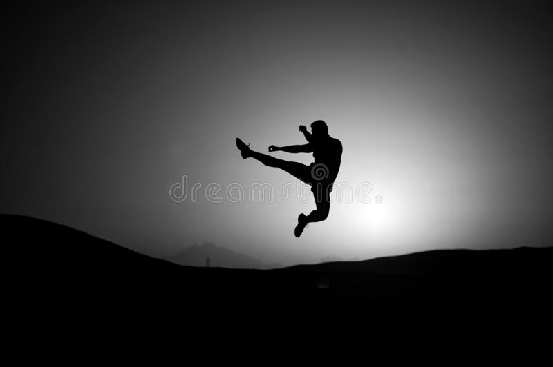 Athlete jump high with energy. Sportsman silhouette on sunset sky. Man training on natural landscape. Workout in summer stock image