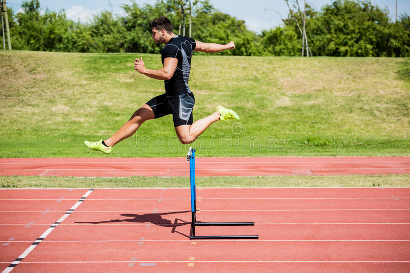Athlete jumping above the hurdle. During the race stock photo