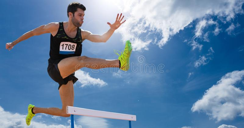 Athlete jumping over hurdles against sky in background stock photo