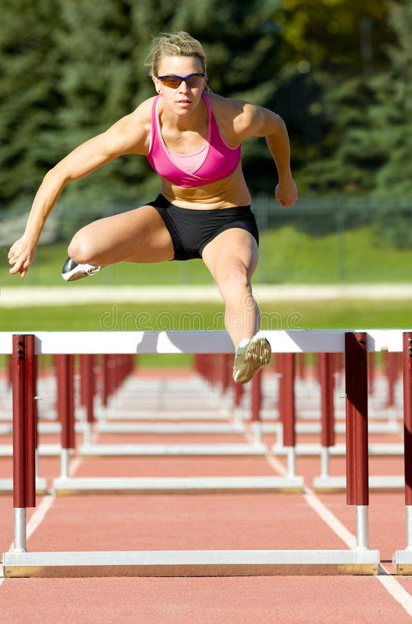 Free Athlete Jumping Over Hurdles On A Track Royalty Free Stock Photography - 17253287