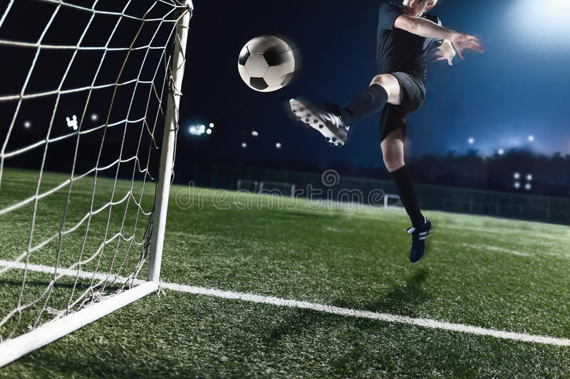 Athlete kicking soccer ball into a goal at night royalty free stock image